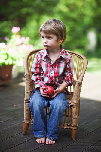 little boy sitting in a wicker chair, holding a red apple