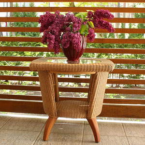 vase of red lilacs on a wicker table
